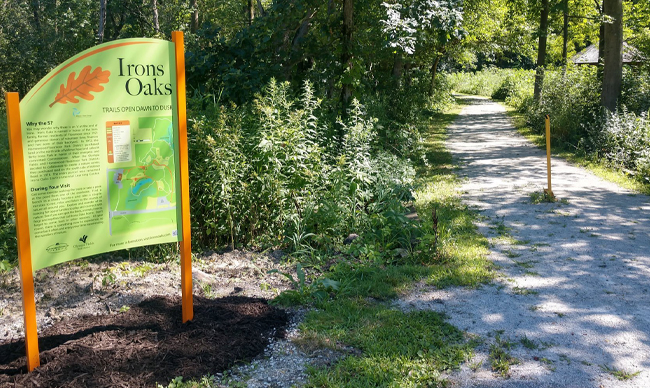 Walking path at Irons Oaks with trail map.